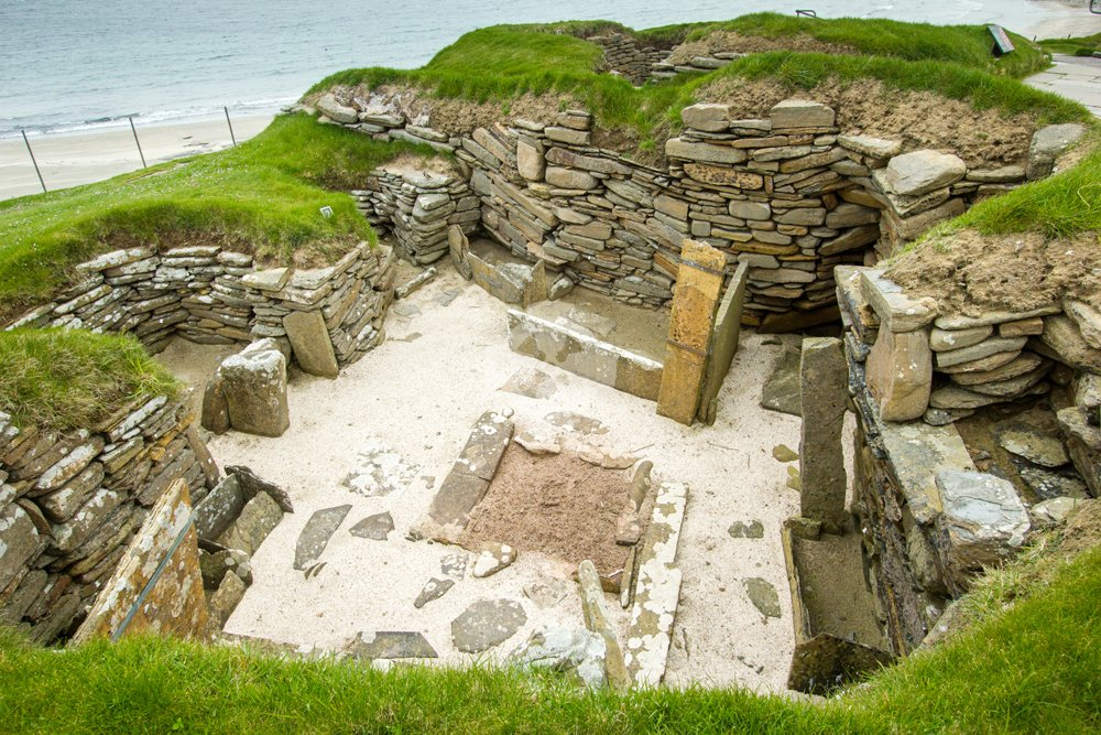 Photo of Skara brae interior showing stone furniture and hearth
