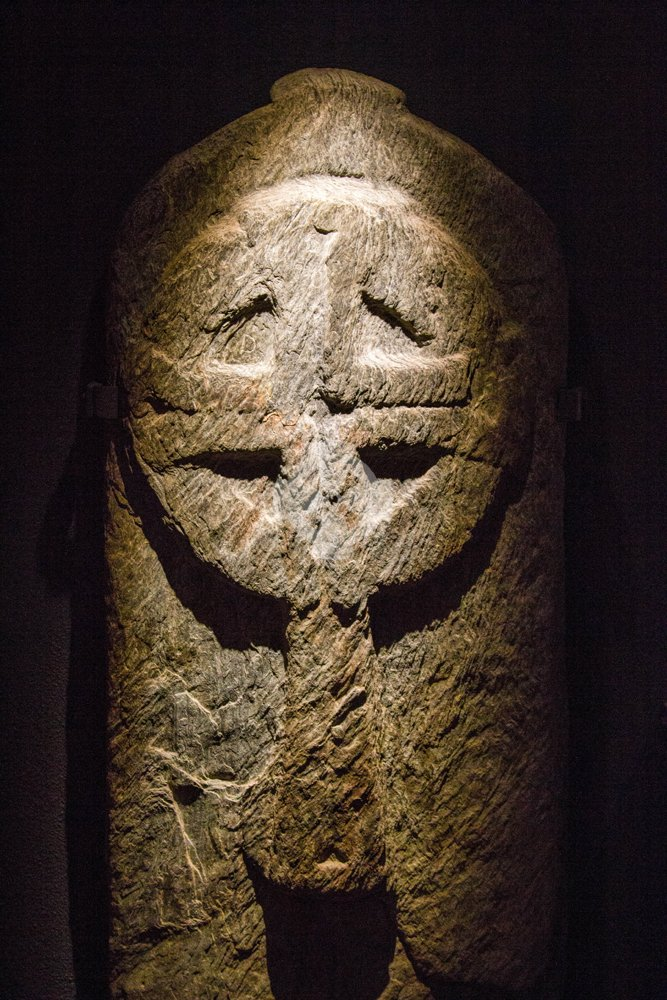photo of carved stone cross, glendalough, ireland kept for protection in the visitor centre